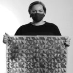 Designer Adrienne Titley holding up a piece of printed textiles